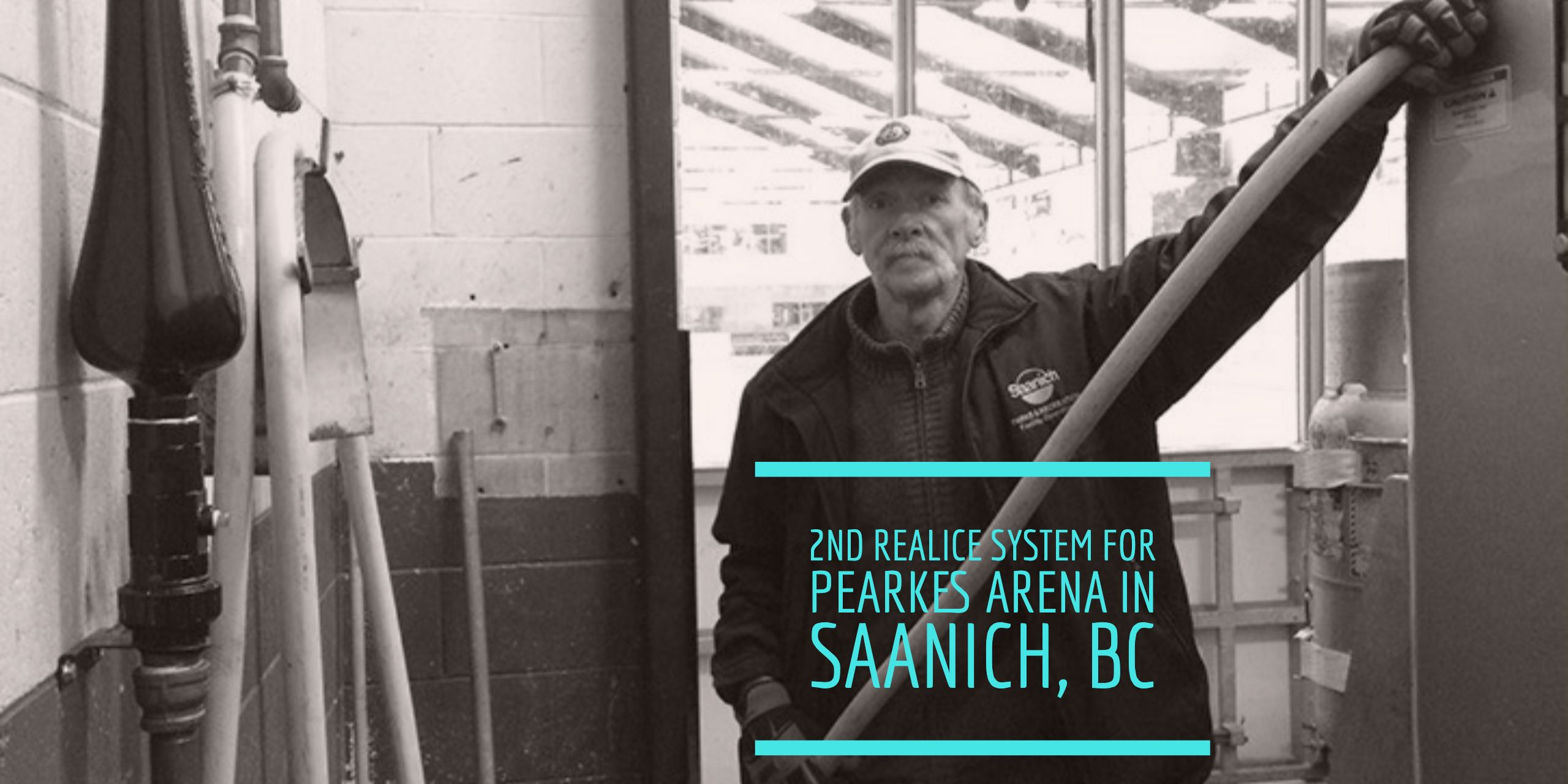 Mike Ross uses a hose connected to the black REALice system at the Gold rink. Now, the arena's Green rink will be equipped also. Photo: Saanich News